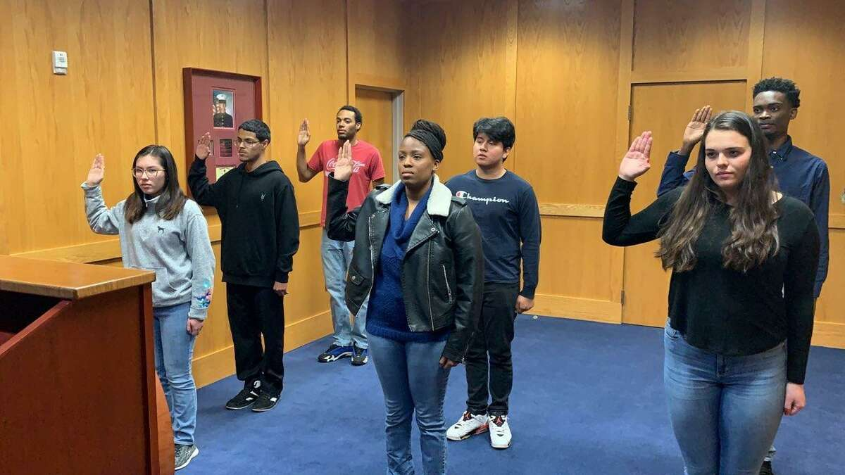 Seven new recruits take an oath after joining the Connecticut National Guard.
