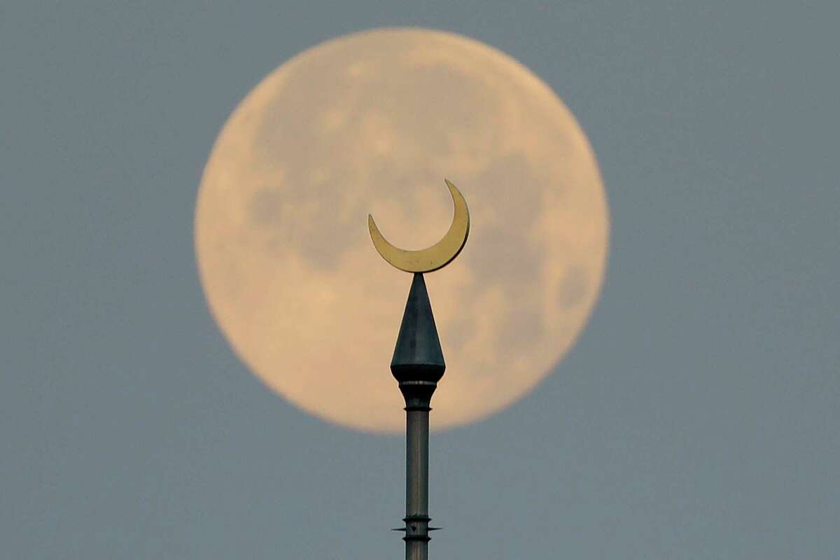 The full pink supermoon sets behind the minarets on the University of Tampa campus Wednesday, April 8, 2020, in Tampa, Fla.
