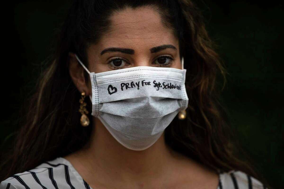 """Jessica Escobar, wears a protective mask with """"Pray for Sgt. Scholwinski"""" written on it during a pray vigil on Wednesday, April 8, 2020, in Humble. Sgt. Scholwinski is in critical condition fighting against Covid-19."""