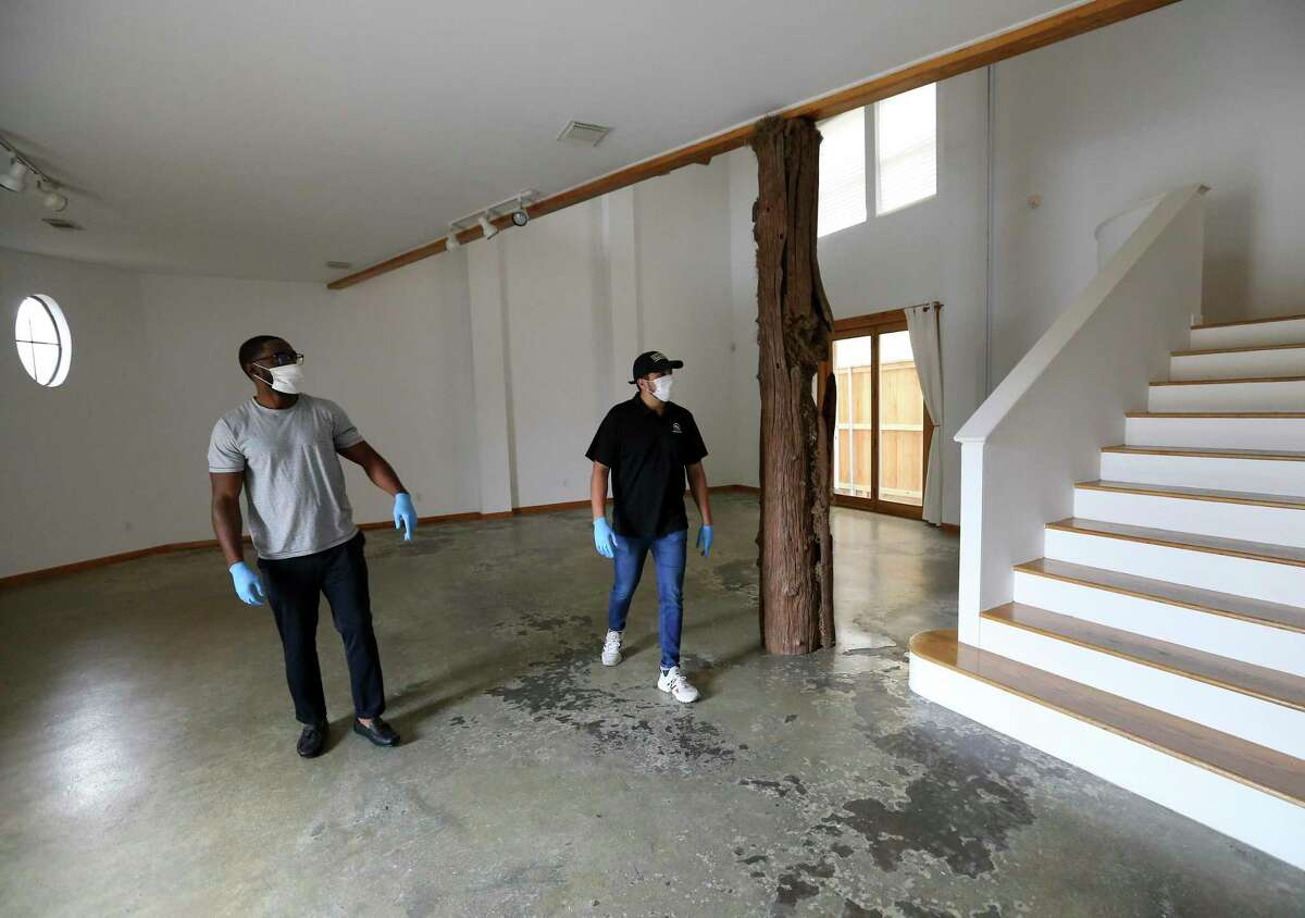 Emmanuel Alia, left, and Jesse Webster wear masks and gloves while viewing a commercial building for their design studio, Prauper Creative, Monday, April 6, 2020, at Rice Military in Houston. Their real estate agent Lily Jang said 99-percent of her showings have been on the internet after the coronavirus outbreak. Her new way of physically showing a property is using disinfectant wipes to clean before opening the door of the building for her client arrives, and then staying outside to wait for her client.