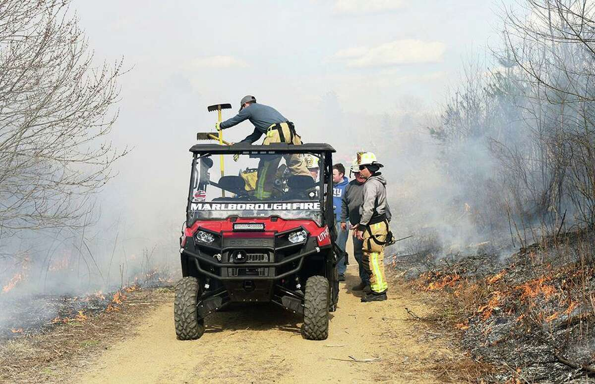 Fire crews work to knock down a 10-acre brush fire Tuesday near the Babcock Pond Wildlife Management Area in East Haddam.