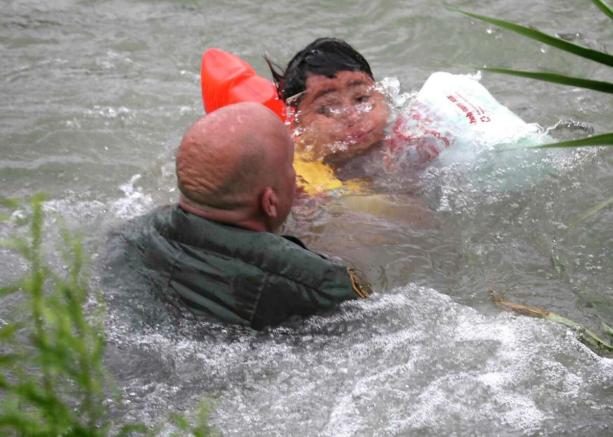 Border Patrol Agent Brady Waikel rescues a 7-year-old boy from Honduras after he fell out of a makeshift raft and lost hold of his mother as Border Patrol agents respond to three rafts crossing the Rio Grande River in Eagle Pass, on Friday, May 10, 2019.