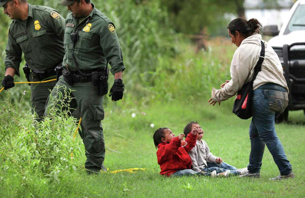 A mother from Honduras goes to her two children, 2 and 4 years old, after Border Patrol agents react to three rafts crossing the Rio Grande River in Eagle Pass, on Friday, May 10, 2019.