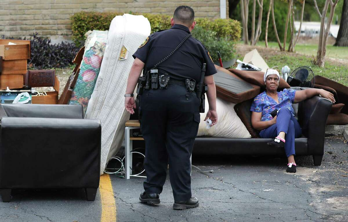 Bexar County Deputy Constable Edward Prado of Precinct 4, center, checks on Patricia A. White as she sits with her possessions after Prado served a writ of possession to White at Brooks Townhomes on Wednesday, Nov. 6, 2019.
