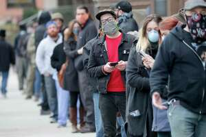People line up to vote in Milwaukee Tuesday. This isn't sustainable in a pandemic, but the nation also isn't prepared to switch to voting by mail.