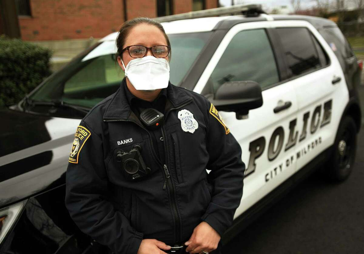 Milford police officer Karen Banks wears a protective mask that she and other officers are required to wear outside their vehicles in Milford, Conn. on Wednesday, April 8, 2020.