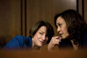 Sens. Amy Klobuchar, D-Minn., and Kamala Harris, D-Calif., speak quietly during a hearing for Supreme Court nominee Brett Kavanaugh in 2018.
