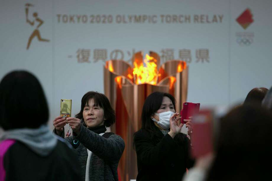 FILE - In this March 24, 2020, file photo, people take pictures with the Olympic Flame during a ceremony in Fukushima City, Japan. The Olympic flame has been removed from public display in Japan, and it's not clear when it will reappear again or where. The flame arrived in Japan from Greece on March 26. (AP Photo/Jae C. Hong, File) / Copyright 2019 The Associated Press. All rights reserved