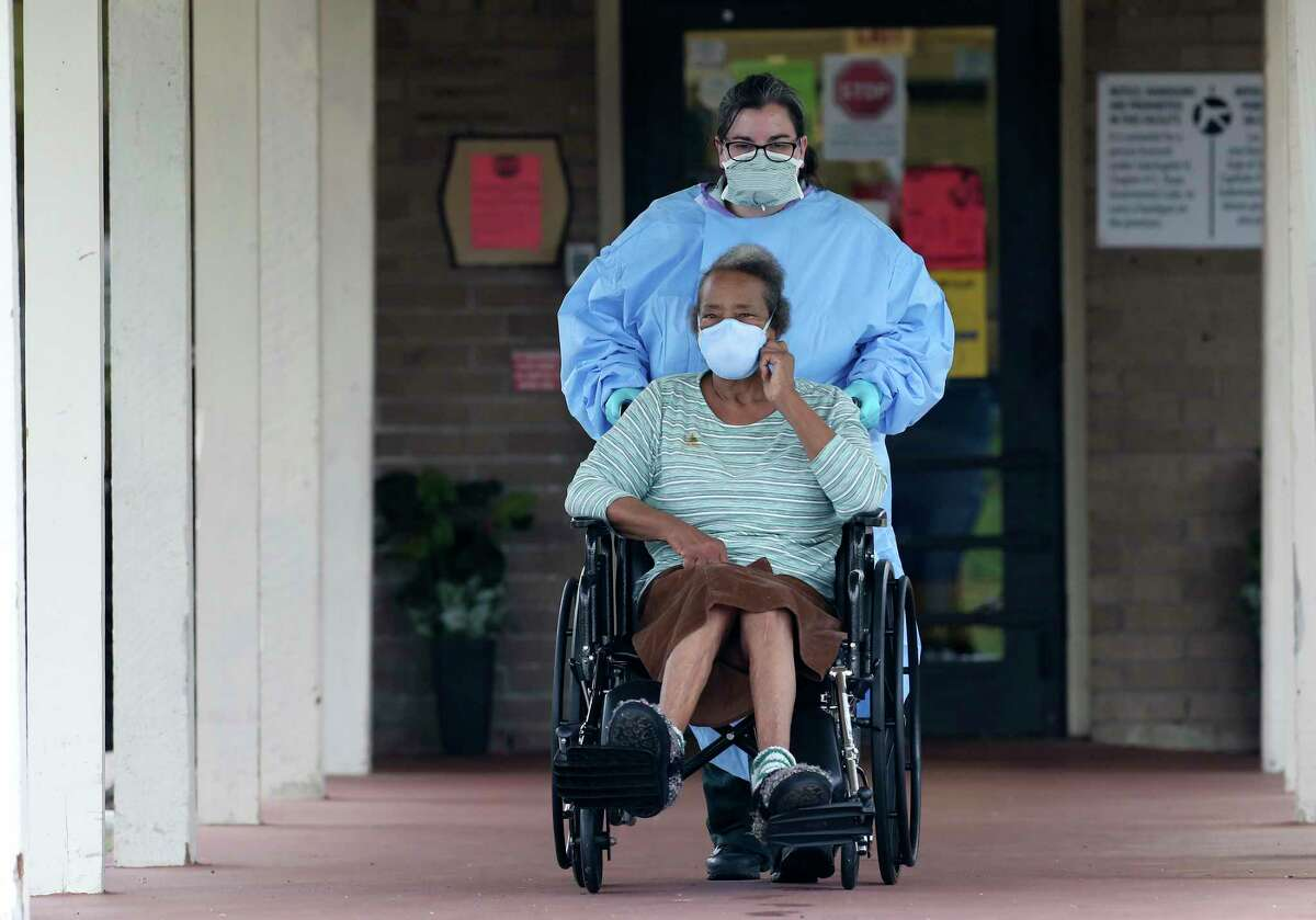 A resident is taken out of the Southeast Nursing and Rehabilitation Center by a private ambulance, Friday, April 3, 2020. According to San Antonio Mayor Ron Nirenberg, 66 of the 84 residents are infected with the novel coronavirus.