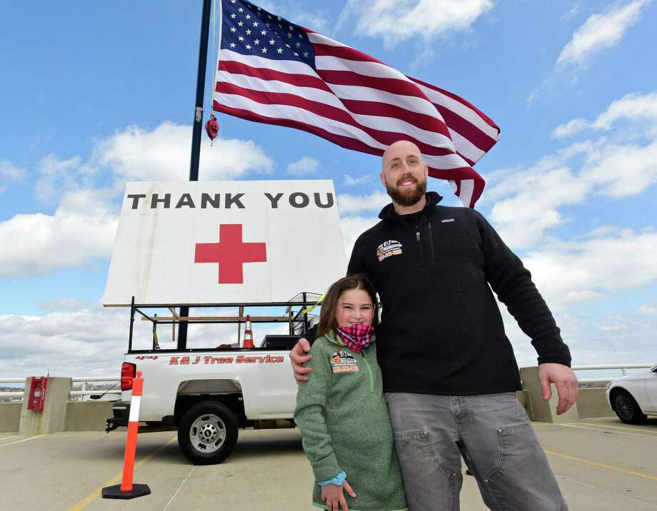 K&J Tree Service owner Kyle DeLucia and his neice Kayla Boyle set up a crane to display a large American Flag and a thank you note for Norwalk Hospital staff Wednesday, April 8, 2020, in Norwalk, Conn. Boyle thought of the idea to thank health care workers during the coronvirus outbreak and helped her uncle paint the sign. Photo: Erik Trautmann / Hearst Connecticut Media / Norwalk Hour