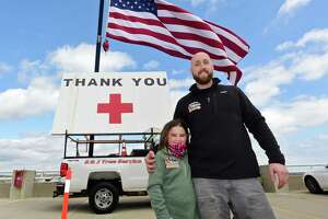 K&J Tree Service owner Kyle DeLucia and his neice Kayla Boyle set up a crane to display a large American Flag and a thank you note for Norwalk Hospital staff Wednesday, April 8, 2020, in Norwalk, Conn. Boyle thought of the idea to thank health care workers during the coronvirus outbreak and helped her uncle paint the sign.
