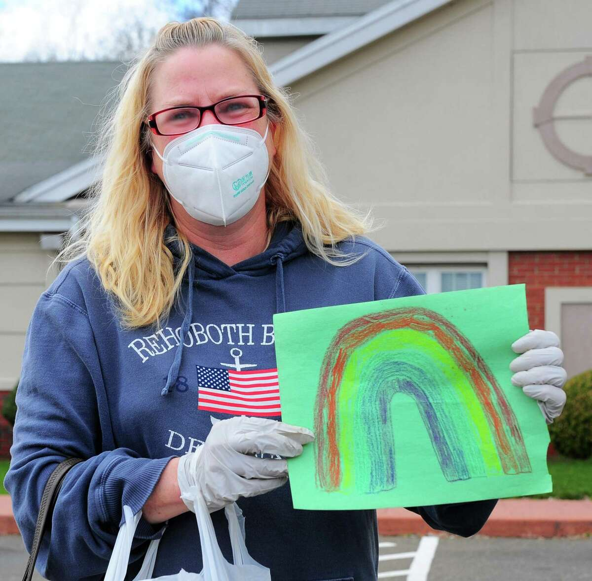Stratford resident Deidre McShea holds up a rainbow drawn by her child at Lord Chamberlain Nursing & Rehabilitation Center in Stratford, Conn., on Wednesday Apr. 8, 2020. McShea arrived to drop off books and the drawing for a resident she is close to. She is unable to physically visit with her because of the lockdown at the center to keep the coronavirus from infecting anyone.