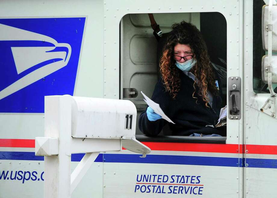 A postal worker wears PPE as she delivers mail in Ansonia, Conn., on Wednesday Apr. 8, 2020. Photo: Christian Abraham / Hearst Connecticut Media / Connecticut Post