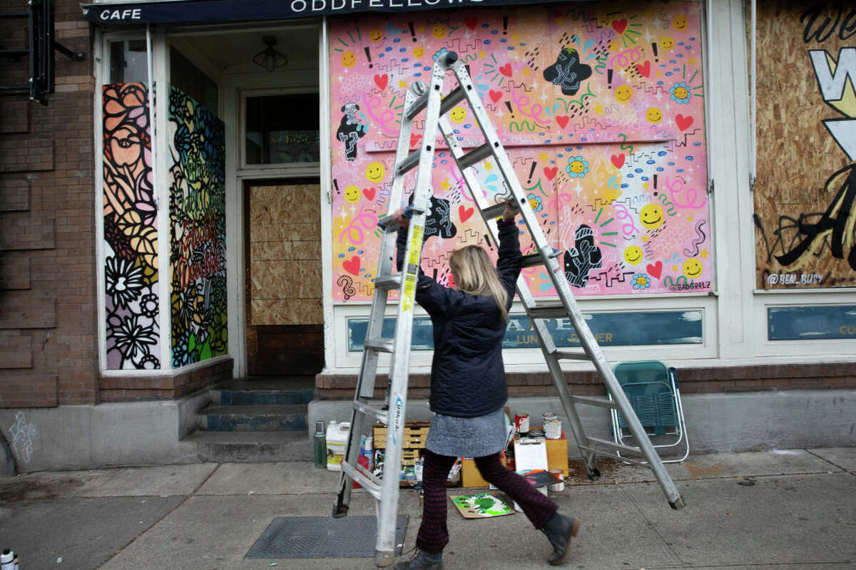 Artist Josephine Rice paints a mural in the boarded up doorway of Oddfellows Cafe and Bar on March 24, 2020 in Seattle. Gov. Jay Inslee issued a Stay at Home order to begin March 25, requiring everyone in the state to stay home for at least two weeks and all non-essential businesses to shut down to help stem the spread of COVID-19.