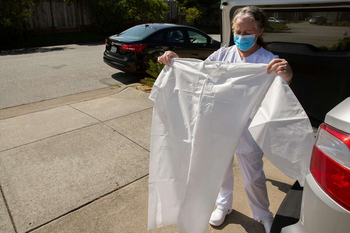 Wendy Barnicoat folds a new gown on Tuesday, April 7, 2020, in Pacifica, Calif. Barnicoat, a phlebotomist for Sanguine Biosciences, came home after drawing blood from a patient who recovered from COVID-19. The blood sample will be used for research.