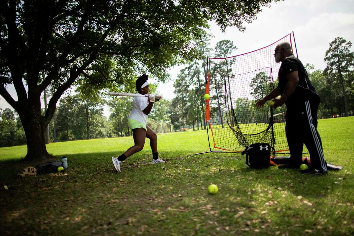 Softball player Victoria Hunter, 14, practices with her father Newal Hunter, 66, at Collins Park, on Wednesday, April 8, 2020, in Spring. The pair mentioned that practicing at their home garage started to feel tight.