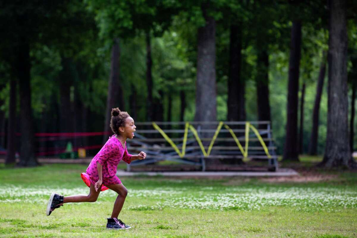 Arielle Goeyns, 6, runs around the Collins Park on Wednesday, April 8, 2020, in Spring. In the background a park seating area has been wrapped in yellow tape to discourage people from using it during the Covid-19 pandemic.