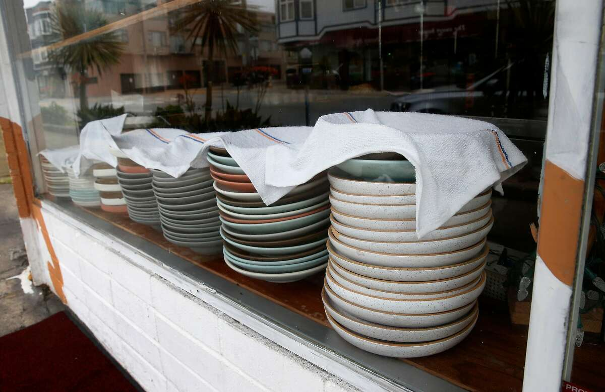 Dishes normally used for dining room service is stacked on the window sill while Cassava restaurant serves take-out orders only on Balboa Street in San Francisco, Calif. on Wednesday, April 8, 2020. Cassava owners have had some of their small business insurance claims denied as the restaurant struggles to stay open by serving take-out orders only during the coronavirus pandemic.
