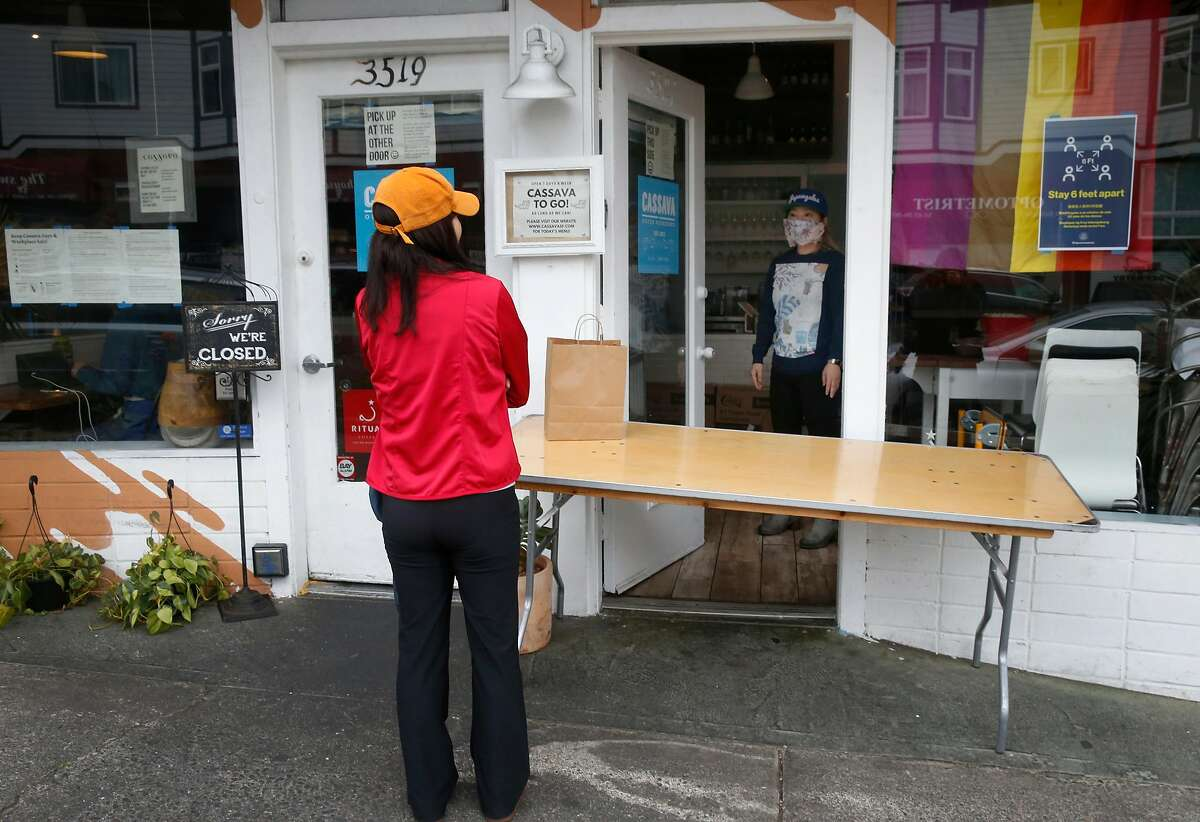 Cassava restaurant co-owner Yuka Ioroi (right) greets a customer picking up a to-go order in San Francisco, Calif. on Wednesday, April 8, 2020. Cassava owners have had some of their small business insurance claims denied as the restaurant struggles to stay open by serving take-out orders only during the coronavirus pandemic.
