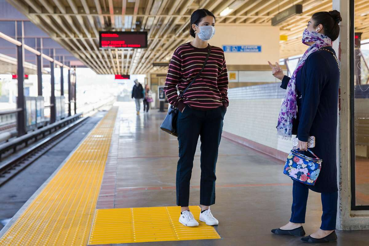 Two friends wear face covers while chatting as they wait for their train at MacArthur BART Station in Oakland, Calif. Friday, April 3, 2020. Although BART has seen a drastic decline in ridership, those who still use their services have been seen wearing protective gear and practicing social distancing.