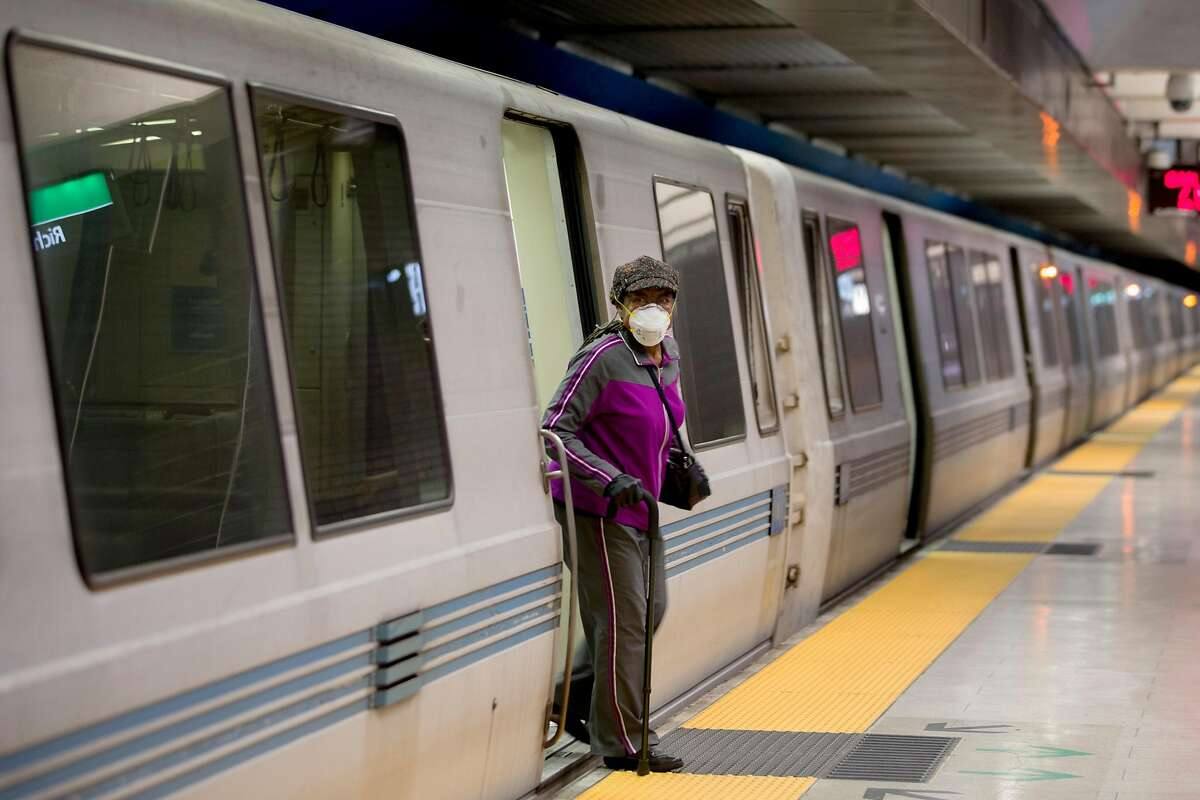 A woman wears a face mask while using a cane to exit a train at 19th Street BART Station in Oakland, Calif. Friday, April 3, 2020. Although BART has seen a drastic decline in ridership, those who still use their services have been seen wearing protective gear and practicing social distancing.