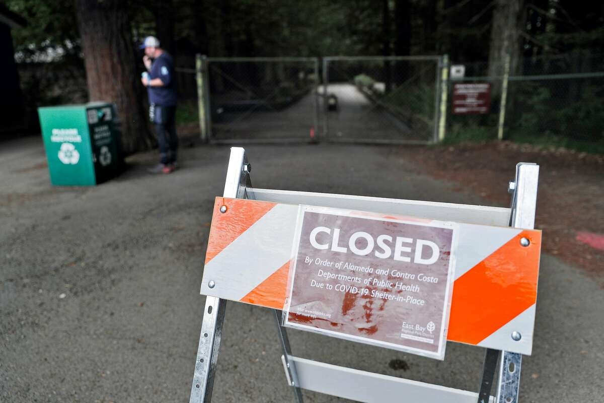 A sign informs visitors at Tilden Regional Park that facilities are closed as people get out of their homes during the statewide shelter in place in Berkeley, Calif., on Sunday, March 22, 2020. The triails at the park remain open, however, for people to get out and exercise.