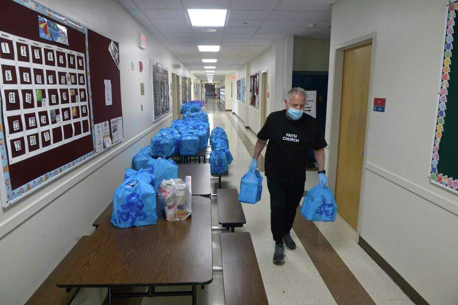 "Charles Spallino, of Danbury, carries out meals to be handed out at the Faith Church ""Manna from Heaven"" program on Wednesday evening. The church was distributing 250 hot meals to people in need. The meals are being purchased from four local restaurants, which also helps those establishments. Wednesday, April 8, 2020, in New Milford, Conn. Photo: H John Voorhees III / Hearst Connecticut Media / The News-Times"