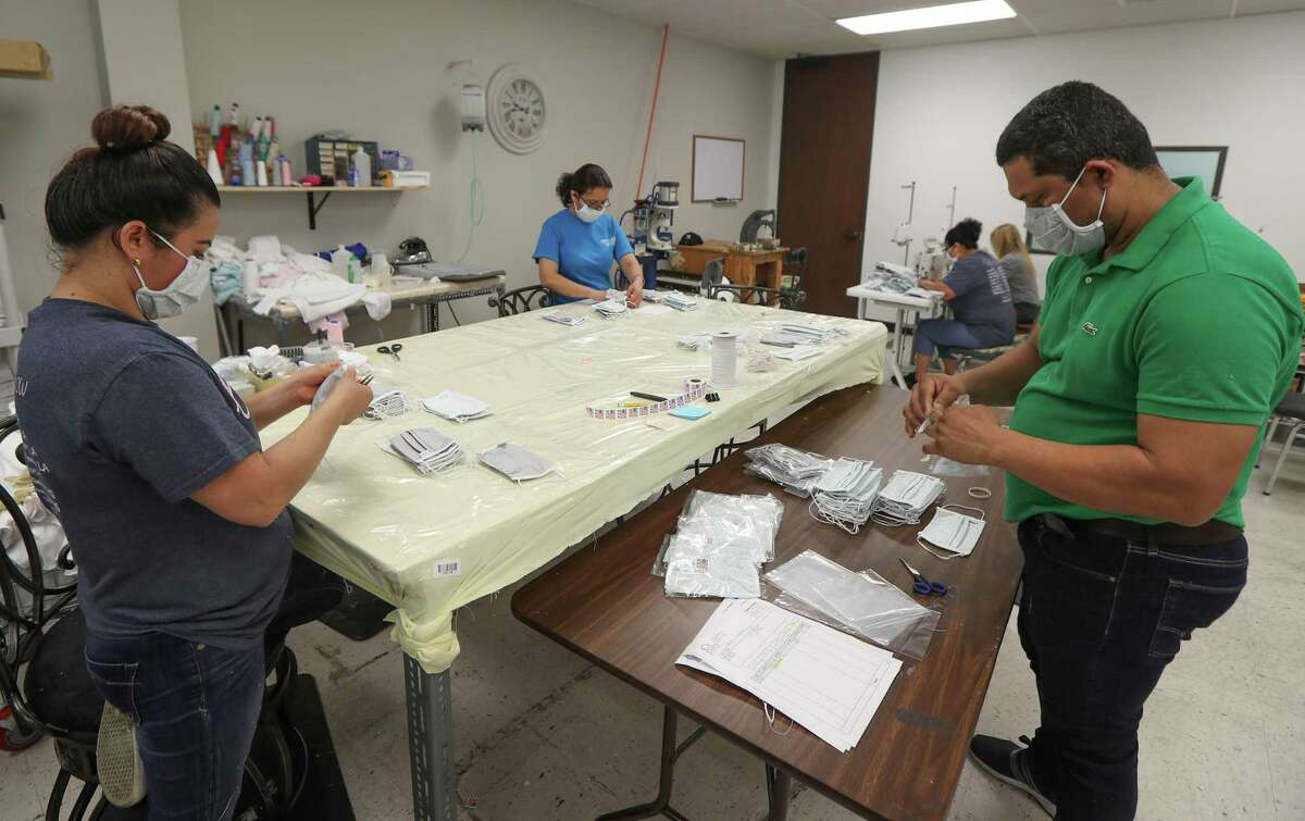 Workers make face masks at Paty, Inc. Thursday, March 26, 2020, in Houston. Paty, Inc. has been manufacturing clothing for 65 years, but as the novel coronavirus has spurred demand for medical supplies, it has retooled its operations to produce face masks and surgical gowns.
