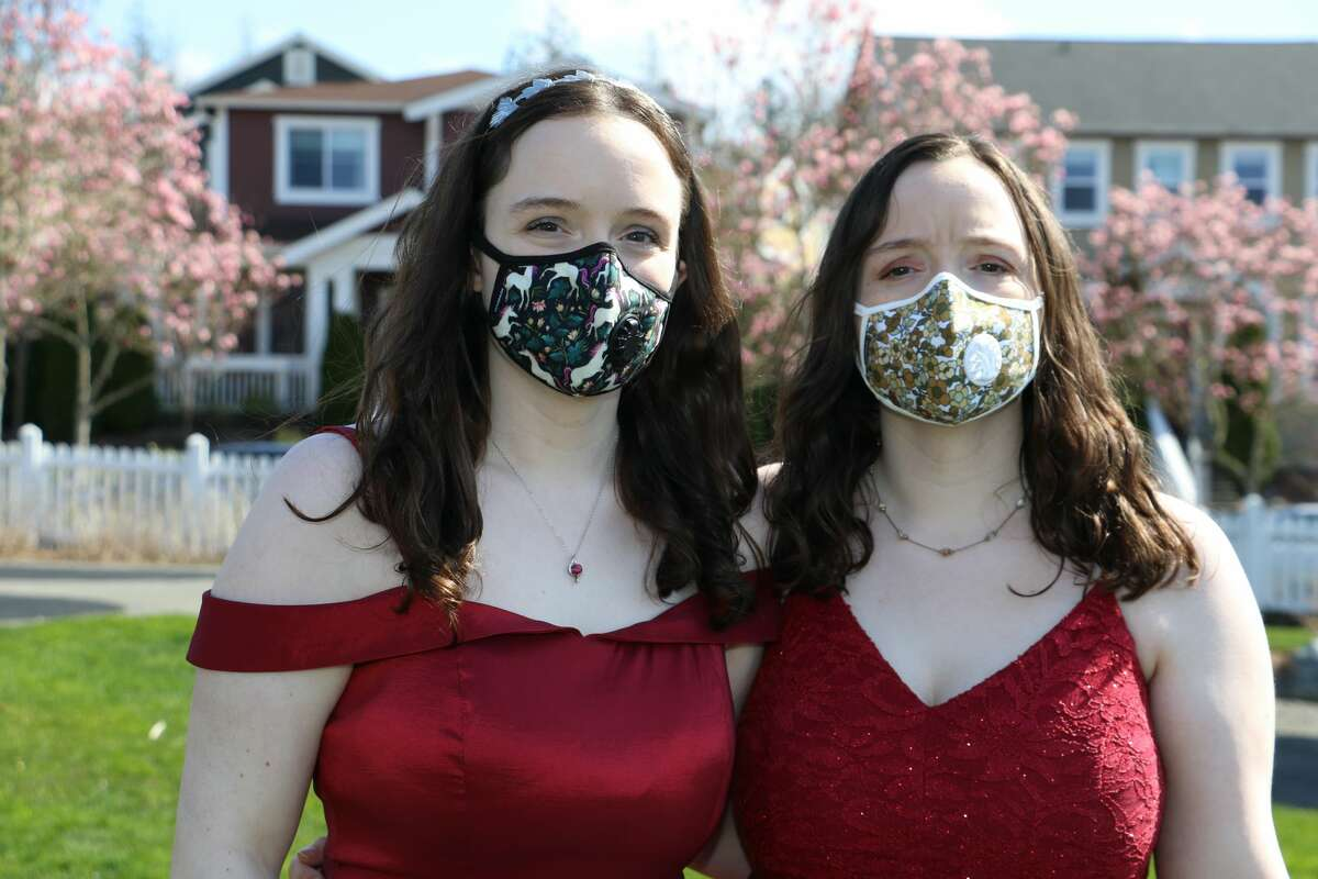 Isabell (left) and Helen Peterson (right) don their prom dresses and face masks in their Issaquah backyard on April 7. Photo courtesy of Shanna Peterson.