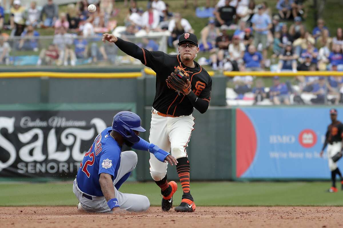 San Francisco Giants' Wilmer Flores forces out Chicago Cubs' Jason Heyward, left, as he turn a double play on Cubs' Victor Caratini during the third inning of a spring training baseball game Tuesday, March 10, 2020, in Scottsdale, Ariz. (AP Photo/Matt York)