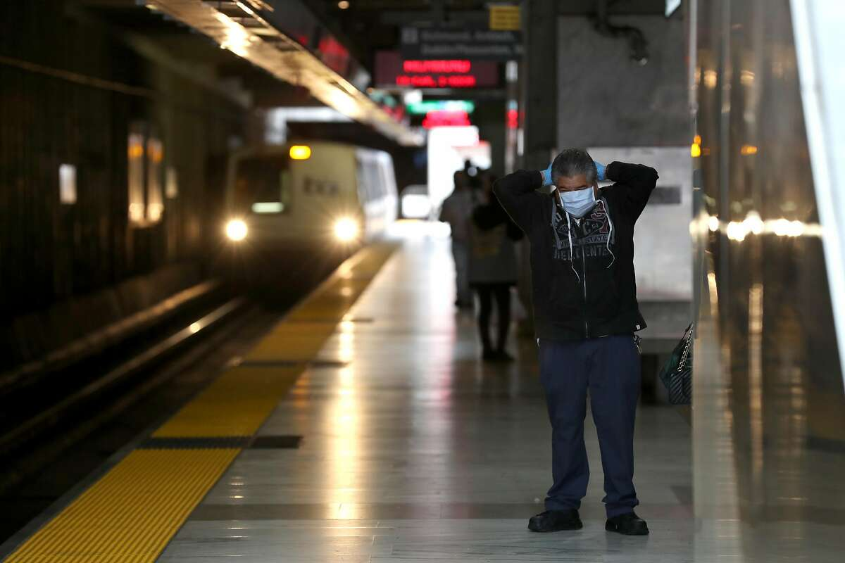 SAN FRANCISCO, CALIFORNIA - APRIL 08: A Bay Area Rapid Transit (BART) passenger adjusts his protective mask as a train pulls into the Balboa Park station on April 08, 2020 in San Francisco, California. BART announced that it is slashing daily service as ridership falls dramatically due to the coronavirus shelter in place order. Starting Wednesday, regular Monday through Friday service will be reduced to running trains every half hour between 5 am and 9 pm. (Photo by Justin Sullivan/Getty Images)
