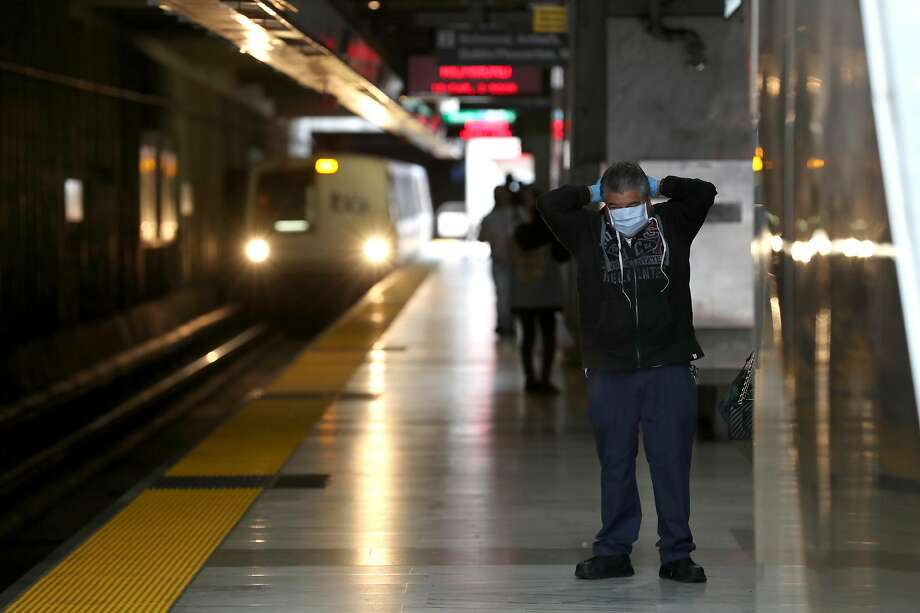 SAN FRANCISCO, CALIFORNIA - APRIL 08: A Bay Area Rapid Transit (BART) passenger adjusts his protective mask as a train pulls into the Balboa Park station on April 08, 2020 in San Francisco, California. BART announced that it is slashing daily service as ridership falls dramatically due to the coronavirus shelter in place order. Starting Wednesday, regular Monday through Friday service will be reduced to running trains every half hour between 5 am and 9 pm. (Photo by Justin Sullivan/Getty Images) Photo: Justin Sullivan / Getty Images