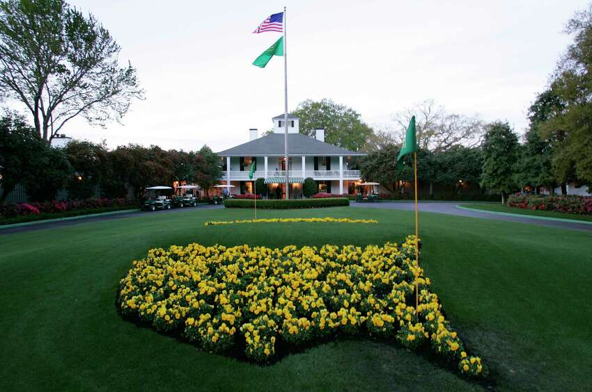 FILE - This April 5, 2006 file photo shows bright yellow flowers in the shape of the United States adorn the lawn at the clubhouse during practice for the 2006 Masters golf tournament at the Augusta National Golf Club in Augusta, Ga. The coronavirus pandemic has killed thousands, forced most everyone to hunker down in their homes, and shut down sporting events around the world. The Masters was not immune to its wrath. (AP Photo/David J. Phillip, File)