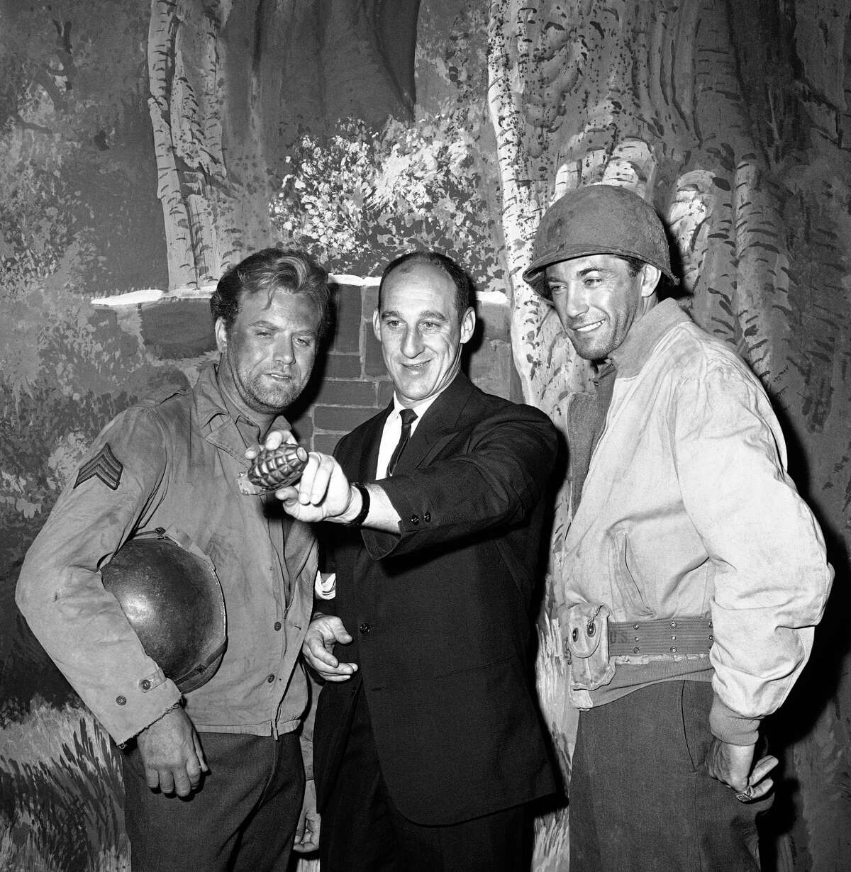 Warren Spahn, Milwaukee Braves pitcher, demonstrates the proper grip for throwing a curve with a grenade to actors Vic Morrow, left, and Rick Jason on the set of the television show,