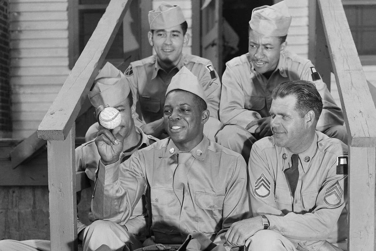 (Original Caption) New York Giant's outfielder Willie Mays, (C) proudly shows some of his new comrades a baseball autographed by all his Giant teammates. Mays reported for Army duty at the Camp Kilmer processing center today.