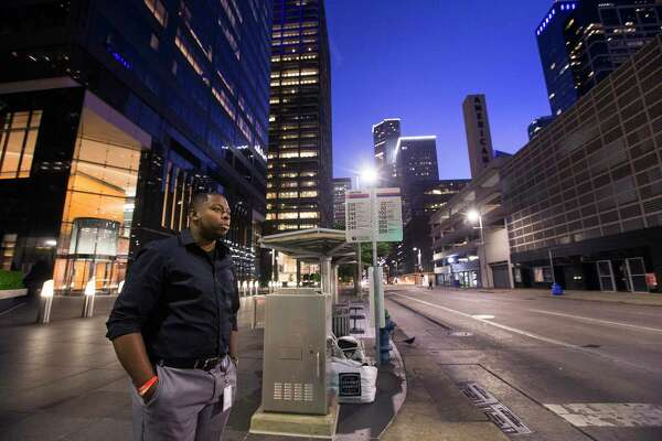 Lee McKelvey, a pipeline control room operator at EVX Midstream, stands on a street corner as he walks to pick up breakfast in a sparsely populated downtown on Wednesday, April 1, 2020 in Houston. With tens of thousands of people working from home due to the conronavirus outbreak, downtown Houston has become a ghost town except for a handful of energy company control room operators, security guards and janitors in the buildings and construction workers in the streets.