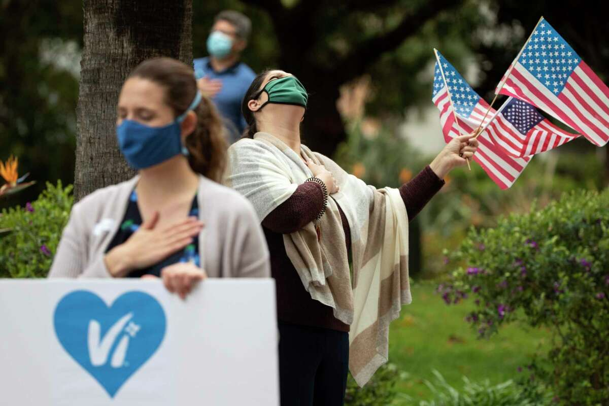 Employees of Vi at La Jolla retirement complex recite the Pledge of Allegiance as they hold signs and wave flags for the residents during an afternoon pep rally, Wednesday, April 8, 2020, in San Diego. Keep scrolling for more good news in the midst of the novel coronavirus.