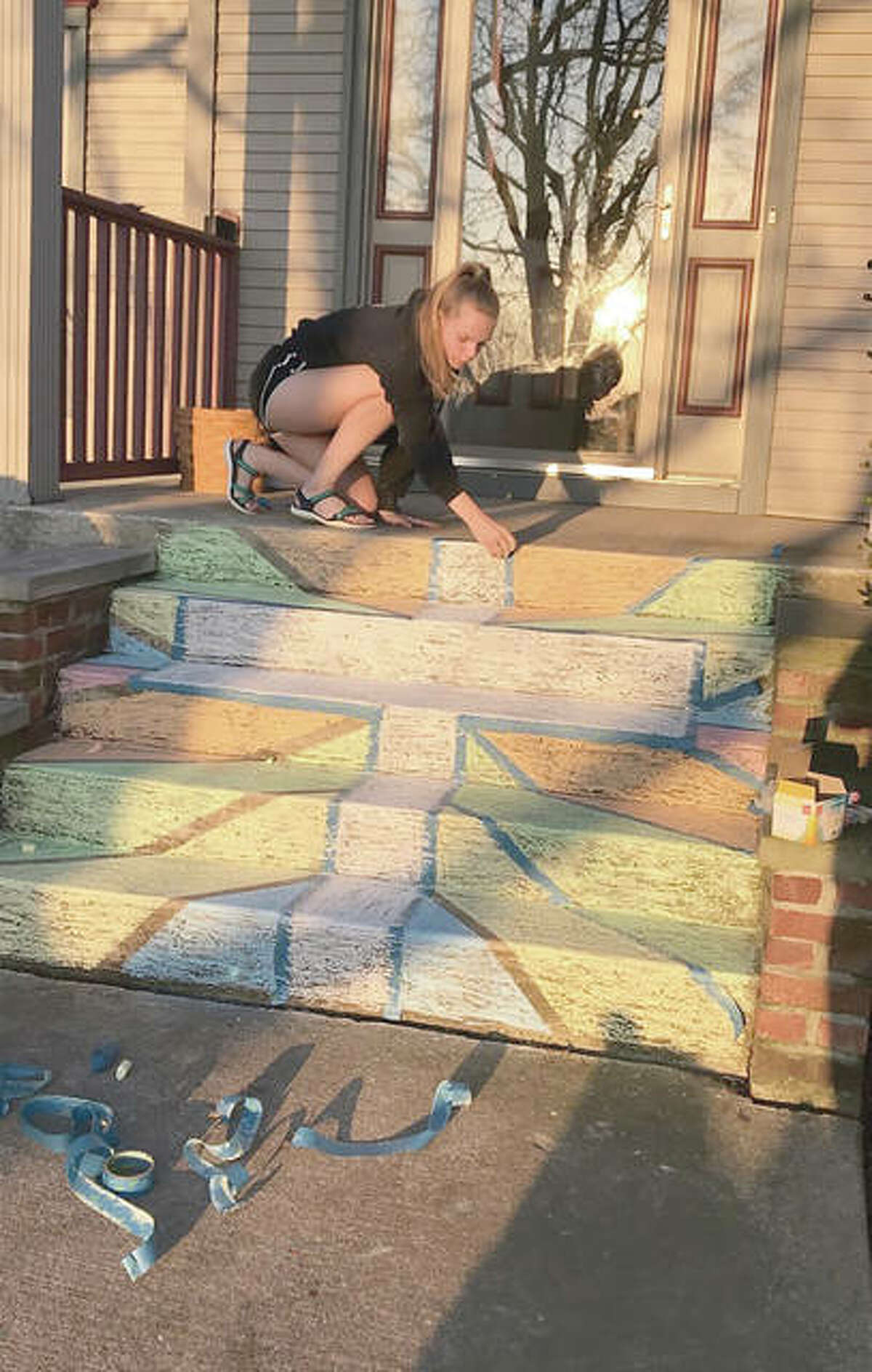 Miley Crow of New Berlin uses chalk to decorate a set of steps with a reminder of Holy Week. Today marks the day many religions commemorate the Last Supper, the final meal Jesus Christ had with his disciples before his arrest and death by crucifixion. Sunday is Easter, which celebrates Christ's resurrection.