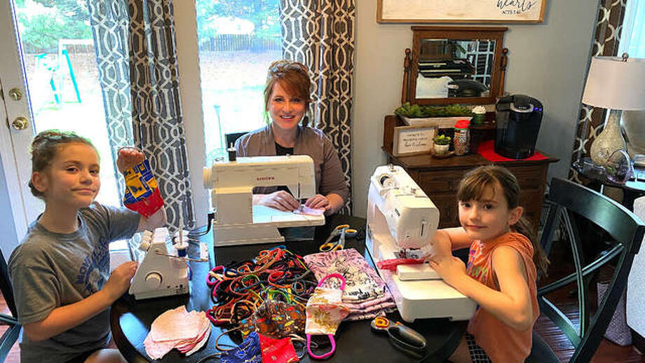 Denise Thibault, middle, works on making masks at home along with her 9-year-old twin daughters Ema, left, and Ava. Thibault recently taught the girls to sew and now they are donating masks to local healthcare professionals and people who are immuno-compromised. Photo: Submitted