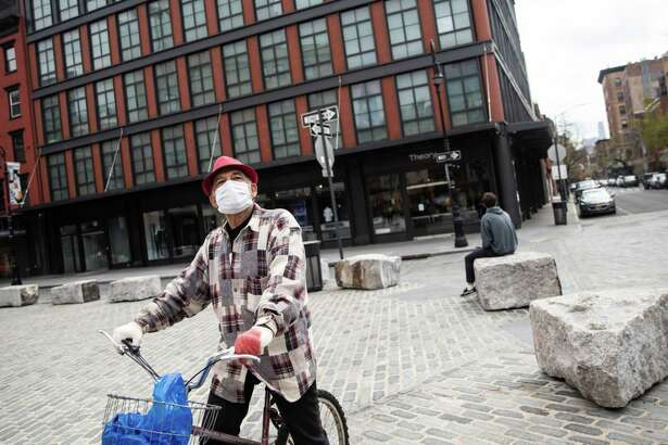 A person wearing a protective mask and gloves rides a bicycle through the Meatpacking District of New York, on April 8. 2020.