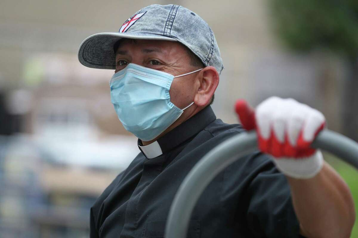The Rev. Pedro López catches his breath as he aided with a food drive to help families at San Pedro Church Wednesday, April 8, 2020, in Pasadena.