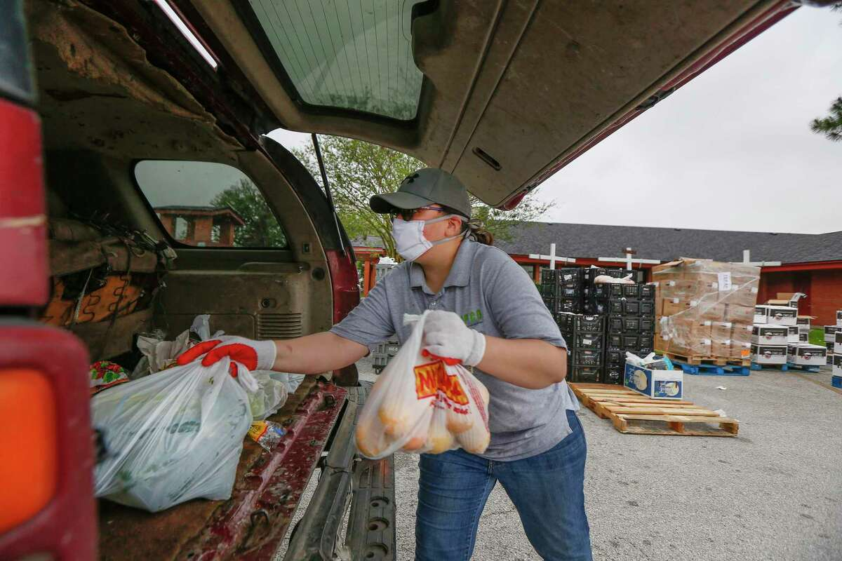 Celia Curiel places fresh food in a vehicle during a food drive to help families at San Pedro Church Wednesday, April 8, 2020, in Pasadena.