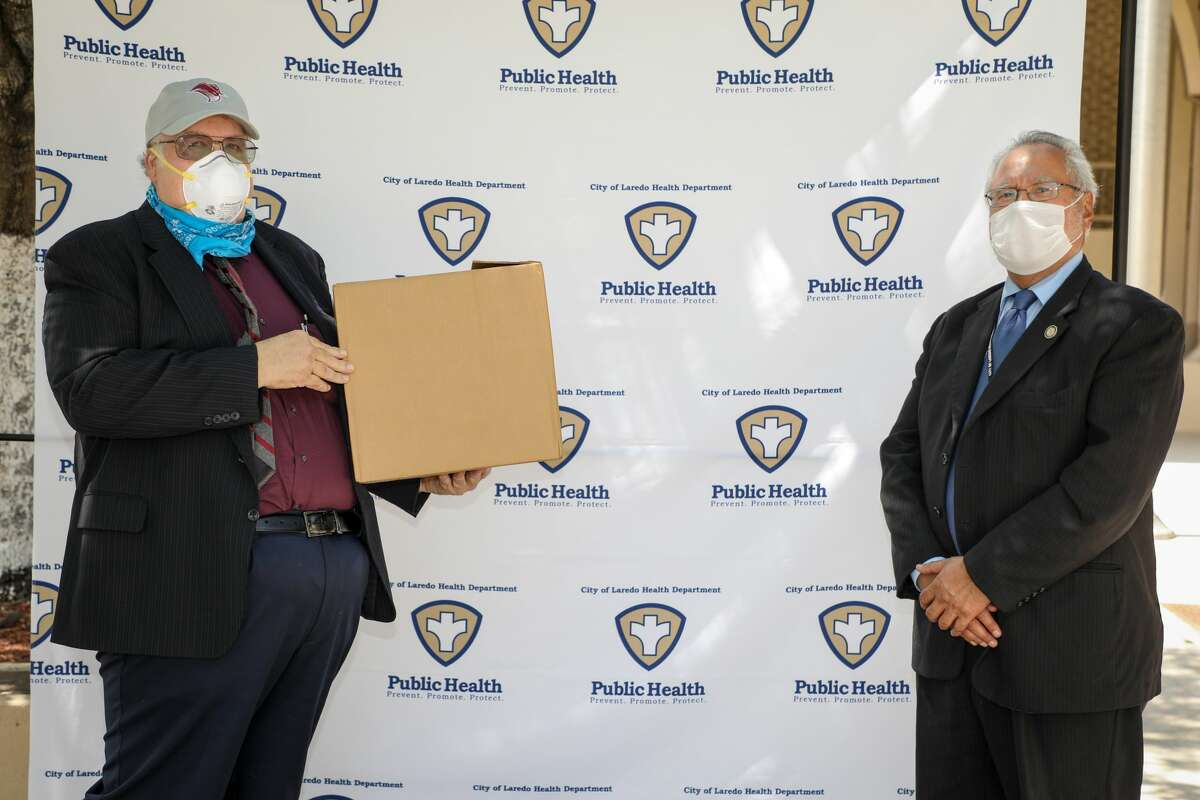 TAMIU President Dr. Pablo Arenaz presents a box full of COVID-19 testing kits to City of Laredo Health Department Director Dr. Hector Gonzalez.