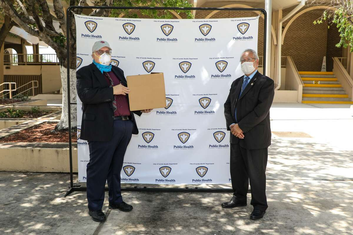 TAMIUPresident Dr. PabloArenazpresents a box full of COVID-19 testing kits to City of Laredo Health Department Director Dr. Hector Gonzalez.