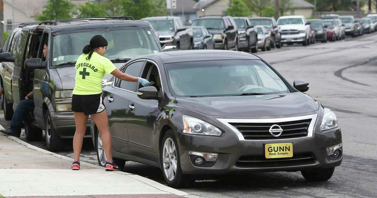 Workers preregister cars in a line stretching for blocks as City Parks and Recreation personnel hand out food stuffs provided by the San Antonio Food Bank for distribution to those in need at Gilbert Garza Park on March 19, 2020.