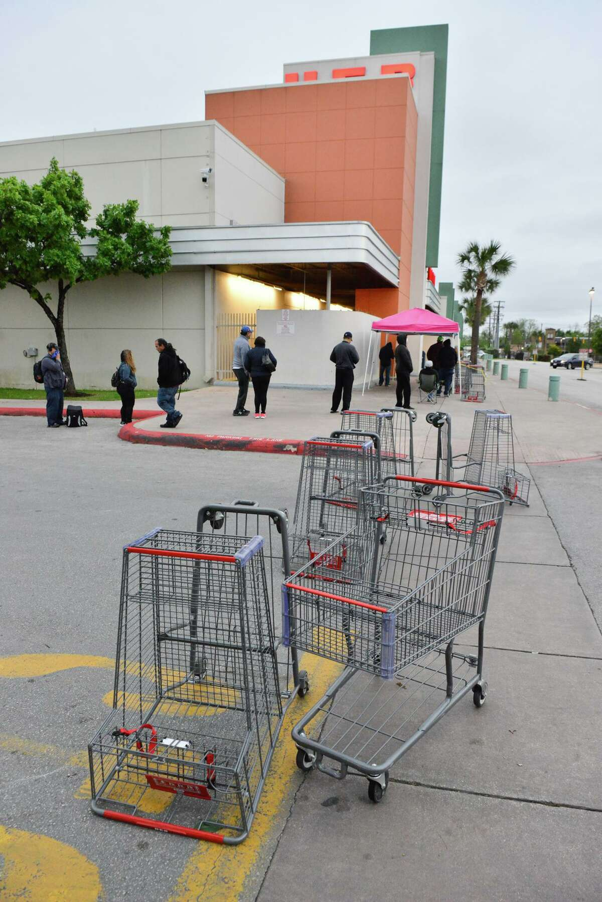 People stand in line waiting for the H-E-B at 2118 Fredericksburg Rd. to open Saturday. Many of those are gig wokers for Instacart, Favor, and Shipt who have no employee benefits yet risk contraction the Covid-19 virus by frequenting heavily-traveled stores.