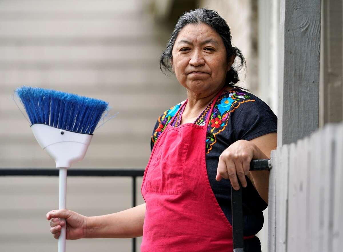 Julia de León posa luego de barrer el balcón del apartamento donde hace la cuarentena por el coronavirus con su hija y yerno en Houston. De León, empleada doméstica, se quedó sin trabajo debido a la pandemia.