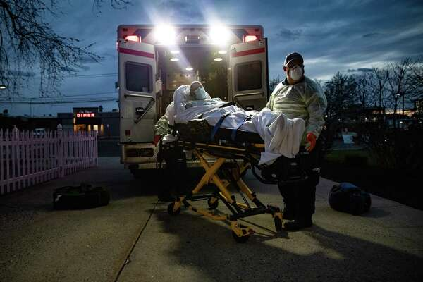 Paramedic David Brody prepares to load a patient with confirmed COVID-19 into an ambulance for transport to Stamford Hospital on April 02, 2020 in Stamford, Connecticut.