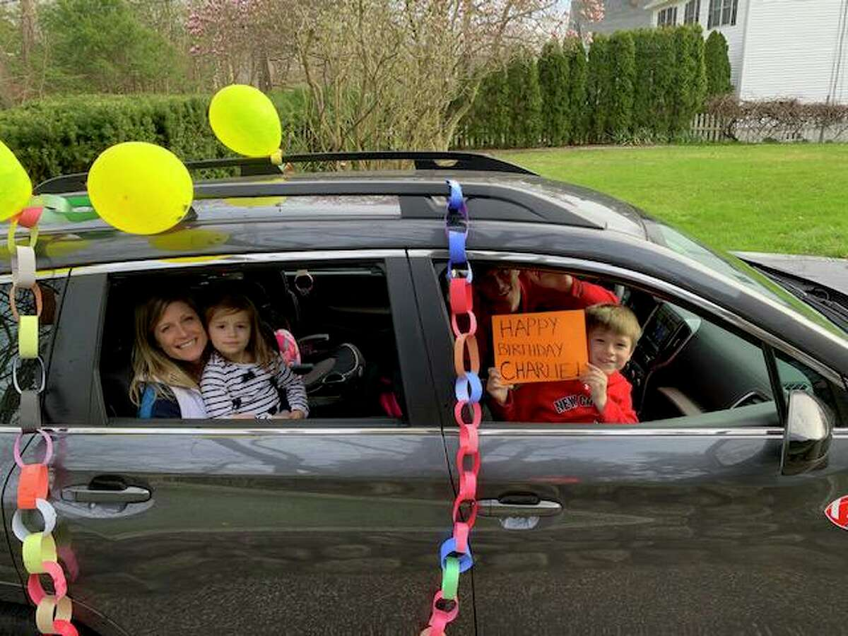 Charlie Silvestri rides in the front seat as he and his family drove around their Stamford neighborhood during his birthday parade.