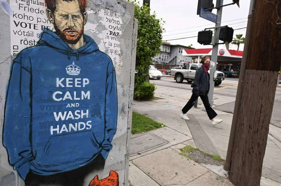 "People walk past graffiti of Prince Harry wearing a hoodie reading ""Keep Calm and Wash Your Hands,"" on April 7, 2020, during the coronavirus pandemic in Los Angeles, Calif. Photo: ROBYN BECK, Getty / AFP or licensors"